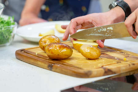 Man hands slicing baked potato on chopping board. Step by step recipe of homemade dish