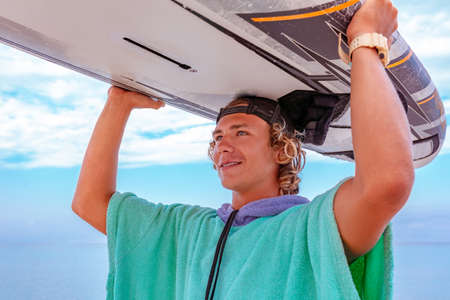 Hübscher Mann, der mit weißem leerem Surfbrett geht, wartet auf Welle, um Fleck am Meeresmeerküste zu surfen. Konzept von Sport, Fitness, Freiheit, Glück, neuem modernen Leben, Hipster.