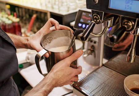 Barista in coffee bar preparing proper cappuccino pouring frothed milk into cup of coffee, making latte art, pattern creation. Professional service, catering concept