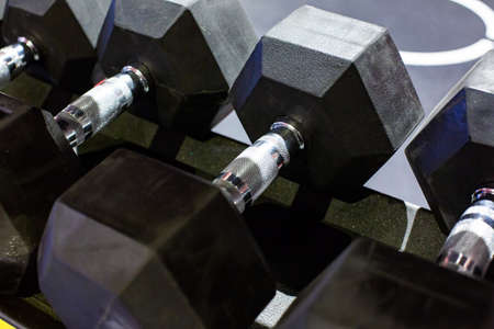 Black rubber dumbbells. Hexagonal heavy duty weight set used for serious hardcore gym workouts, cross fit training and workout routines