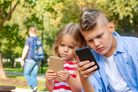 Busy kids looking at their phones texting sms and playing sitting outside