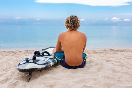 Handsome man sits on the beach with white blank surfing board wait for wave to surf spot at sea ocean shore. Concept of sport, fitness, freedom, happiness, new modern life, hipster.