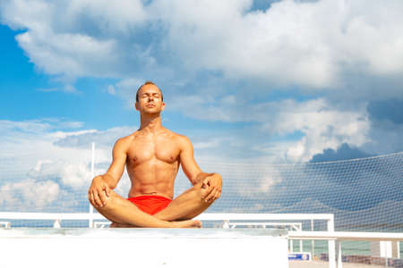 Handsome Shirtless Young Man During Meditation or Doing an Outdoor Yoga Exercise Sitting against the blue sky.
