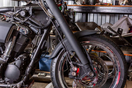Cropped close up shot of beautiful and custom made motorcycle in the workshop Stock Photo