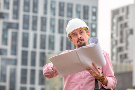 Portrait of architect at work with helmet in a construction site, reads the plan, paper projects Banco de Imagens