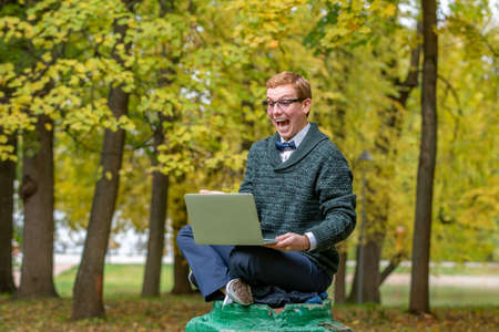 A man with lap top on a pedestal who pretends to be a statue in the the autumn park. Get idea 免版税图像