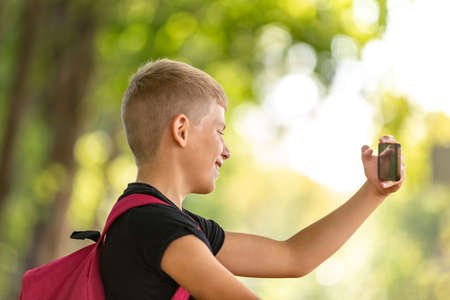 young happy preteen boy walking in warm sunny summer day in the park and taking selfie on smartpone 스톡 콘텐츠