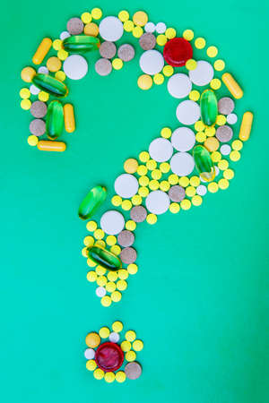 Pills and capsules forming a question mark