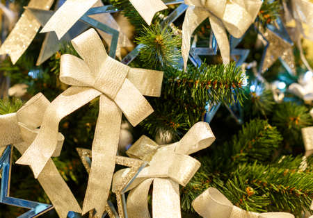 Christmas tree with shiny bows. Concept New Year celebration background. Closeup photo of christmas tree decorated with shiny bows