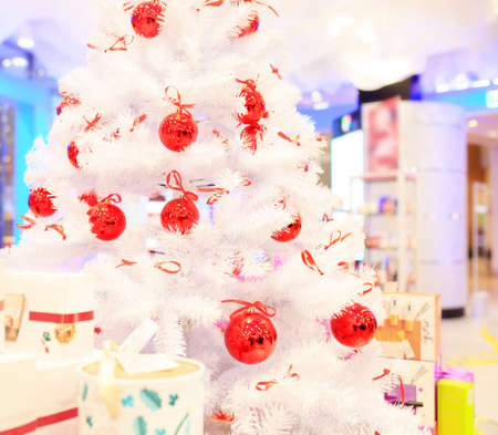 Christmas tree with red balls. Christmas tree with red balls. Concept New Year celebration background. White christmas tree decorated with red balls with colorful gift boxes