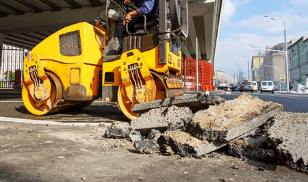 Asphalt compactor in the city. Road roller working at road construction site
