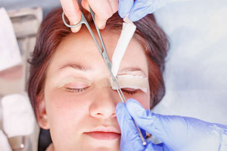 Surgeon applies a bandage to the female patients eyelids after