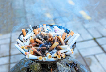 Cigarette butts at ashtray. Close up heap of many smoking cigarettes stubs, cigarette butts in ashtray