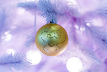 Christmas tree with golden balls. Concept New Year celebration background. Closeup photo of white christmas tree decorated with golden balls