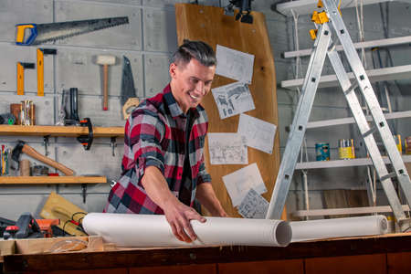 A carpenter works. Carpenter studying drawing project. Against the background of the workshop