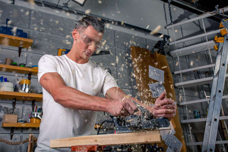 A carpenter works on woodworking the machine tool. Saws furniture details with a circular saw. Process of sawing parts in parts. Against the background of the workshop Stockfoto