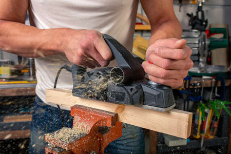 A carpenter works on woodworking the machine tool. Saws furniture details with a circular saw. Process of sawing parts in parts. Against the background of the workshop