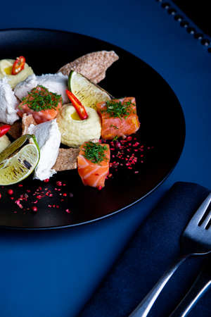 delicious salmon with pate and hummus in restaurant background. Healthy exclusive food on big black platter closeup