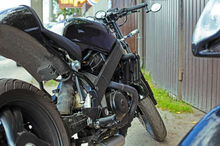 Cropped close up shot of beautiful and custom made motorcycle parked on the street