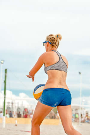 Volleyball beach player is a female athlete volleyball player getting ready to serve the ball on the beach. Stock Photo