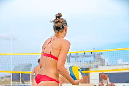 Volleyball beach player is a female athlete volleyball player getting ready to serve the ball on the beach. 写真素材