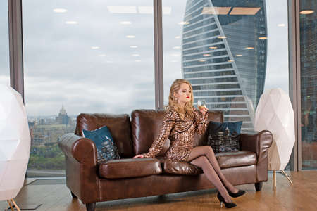 young beautiful blonde woman sits on a leather sofa with a glass of champagne against the background of a panoramic window overlooking the skyscrapers and a big city.