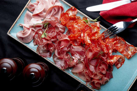 assorted cold meat, prosciutto, slices ham, beef jerky, salami, meat and mustard on black background. Meat appetizer, catering food concept. Фото со стока
