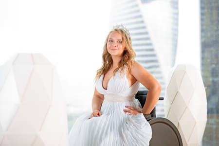 Beautiful disabled bride posing in a wheelchair against the background of a panoramic window overlooking the skyscrapers and a big city, she is smiling at camera, disability overcoming concept