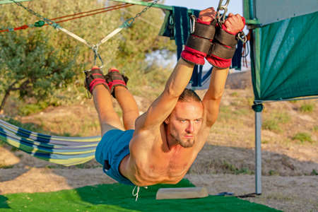 Yoga treatment for core, yoga swing, slim young man strapped to four planks above the ground, man developing endurance and stretching core Reklamní fotografie