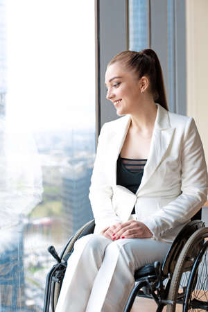 Invalid or disabled young business woman person sitting wheelchair in office