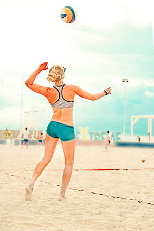 Volleyball beach player is a female athlete volleyball player getting ready to serve the ball on the beach. 免版税图像