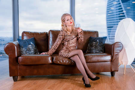 A beautiful young blonde girl in a fashionable dress, posing on a leather sofa with a glass of champagne against the background of a panoramic window overlooking the skyscrapers Stock Photo