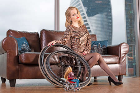 A beautiful young blonde girl in a fashionable dress with a disability, posing on a leather sofa against the background of a panoramic window overlooking the skyscrapers