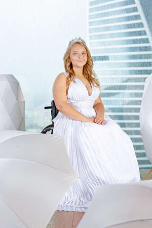 Beautiful disabled bride posing in a wheelchair against the background of a panoramic window she is smiling at camera, disability overcoming concept