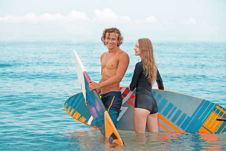Surfisti in spiaggia - Coppia sorridente di surfisti che camminano sulla spiaggia e si divertono in estate. Sport estremo e concetto di vacanza