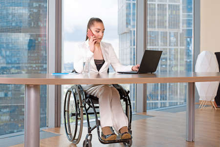 Invalid or disabled young business woman person sitting wheelchair working in office on a laptop
