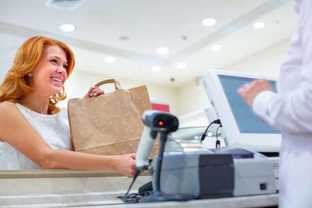 Pago inalámbrico mediante smartphone y tecnología NFC. De cerca. Clienta pagando con teléfono inteligente en la tienda. Cerrar compras Foto de archivo