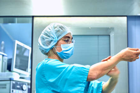 Female Surgeon in a medical mask and in a suit in the hospital washing thoroughly her hands before performing a surgery