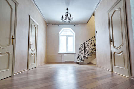 Entrance hallway with staircase. View of steps with wrought iron railings