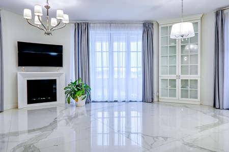 Intérieur minimaliste du salon dans des tons clairs avec sol en marbre, grandes fenêtres et cheminée sous TV
