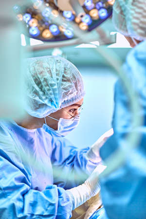 Close up portrait of young female surgeon doctor wearing protective mask and hat during the operation. Healthcare, medical education, surgery concept Imagens