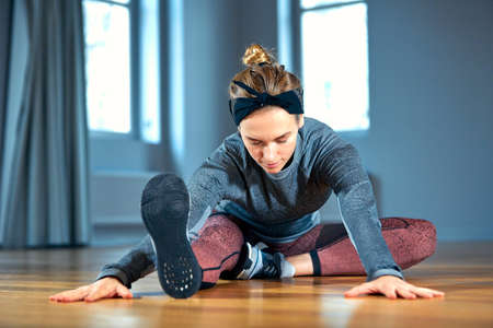 Young beautiful woman in sportswear doing stretching while sitting on the floor in front of window at gym Stock Photo