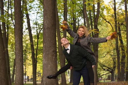 Happy young couple playing with fallen leaves in autumn park