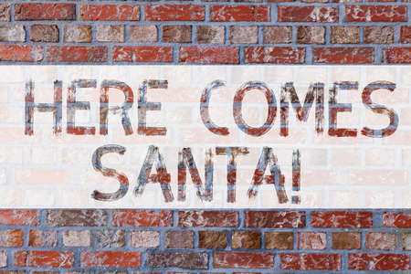 Handwriting text writing Here Comes Santa. Concept meaning Christmas song written and performed by Gene Autry Brick Wall art like Graffiti motivational call written on the wall