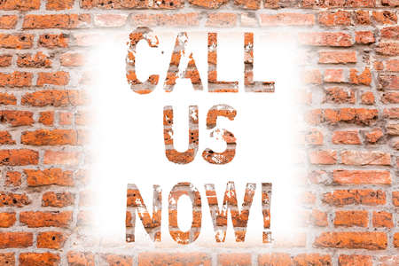 Text sign showing Call Us Now. Conceptual photo Communicate by telephone to contact help desk support assistance Brick Wall art like Graffiti motivational call written on the wall Stock Photo