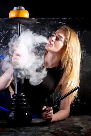 Young, beautiful woman smokes a hookah in cafe. It produces smoke from his mouth. The pleasure of smoking.