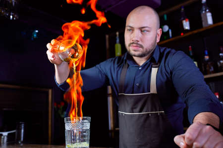 Fiery show at the bar. The bartender makes hot alcoholic cocktail and ignites bar. Bartender prepares a fiery cocktail. Fire on bar. Фото со стока