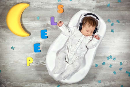 Newborn baby sleeps in a special orthopedic mattress Baby cocoon, on a wooden floor multicolored letters around. Calm and healthy sleep in newborns.