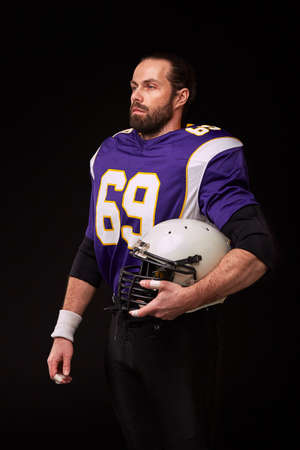 Configured for the game. American football player looking at camera and holding helmet in his hand while standing against black background Stock Photo