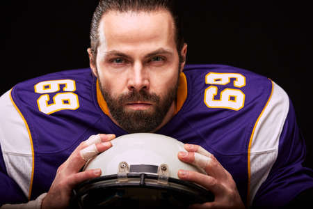 Portrait of american football player with helmet in hand close up